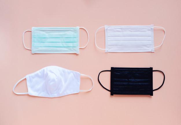 Na foto, da esquerda para a direita: máscara cirúrgica, máscara de TNT e máscaras de pano em diferentes formatos abaixo.